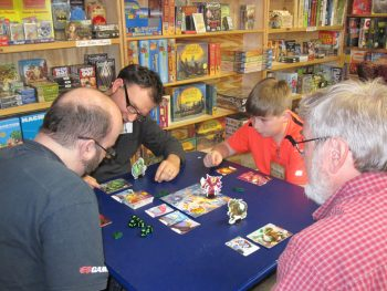 Gamers of all ages play games at Here Be Books & Games' Game Night